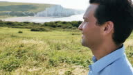 Pensive man, looking into the distance. Head and shoulders. Beautiful coastal location.  Slow mo. WS.