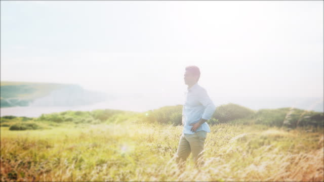 Pensive man, walking, standing and looking into the distance. Beautiful coastal location.  Slow mo. WS.