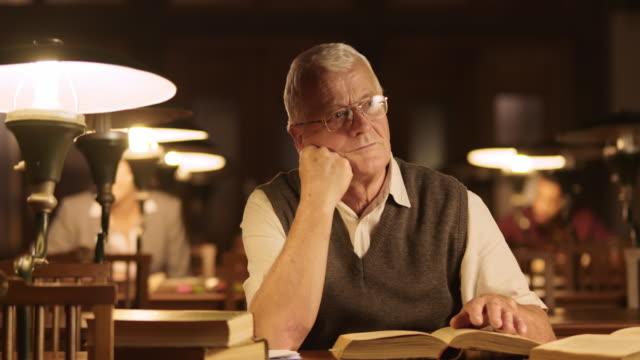 DS Pensive senior man in bibliotheek het neerschrijven van zijn gedachten
