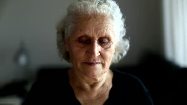 Pensive senior woman portrait drinking tea and looking around
