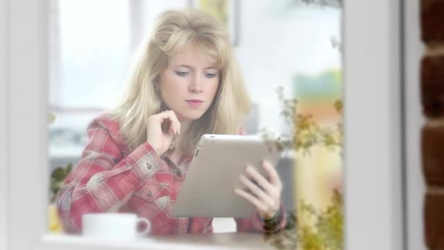 Pensive tablet girl, window reflections.