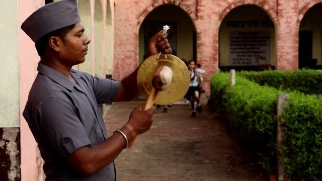 Peon ringing bell in school, Haryana, India
