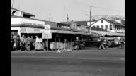 People and cars passing by Fisherman's wharf restaurants and shops Fisherman's wharf restaurants and shops on January 01 1940 in San Francisco...
