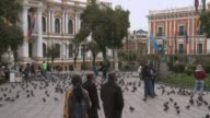 People and pigeons passing by in Murillo Square in the city center of La Paz Bolivia
