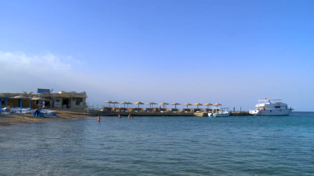 WS PAN People and tourist boat at red sea bay / Hurghada, Red Sea coast, Egypt