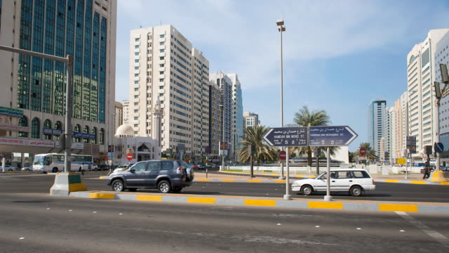 T/L of people and traffic at intersection of Hamdan Bin Mohamed Street and Rashid Bin Saeed Maktoum Street, Abu Dhabi, United Arab Emirates