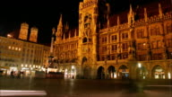 People and traffic move through the plaza in front of Neues Rathaus in Marienplatz, Munich, Germany.