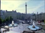 People and traffic stream around Trafalgar Square London