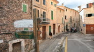 WS People and vehicles on narrow street between buildings in village Fornalutx near Soller / Mallorca, Balearic Islands, Spain