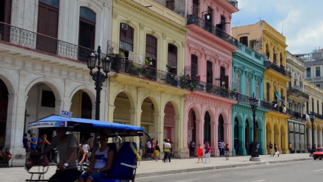 MS People are walking on road of havana cuba colorful downtown pastel buildings near capital homes / Havana, Cuba