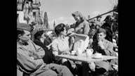 People at open air cafe tables / people walk along rubble filled streets / soldiers sitting at table smiling while companion talks to the camera /...