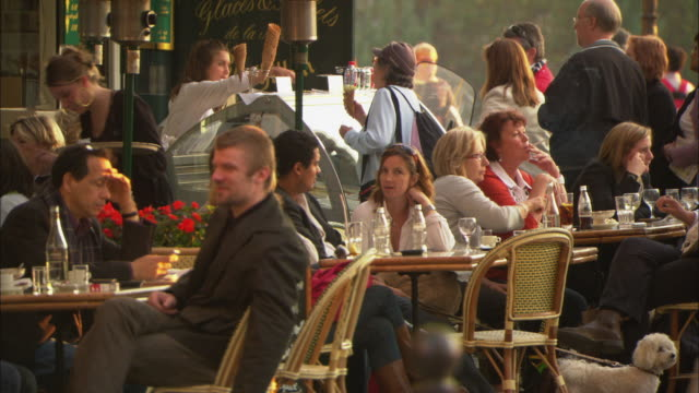 MS SELECTIVE FOCUS People at outdoor cafe, woman serving ice cream / Paris, France