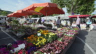 People at weekly street market at flower stall