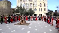 People attend Newroz celebrations around the Maiden Tower in Baku Azerbaijan on March 18 2017 Celebration starts after Azerbaijani President Ilham...