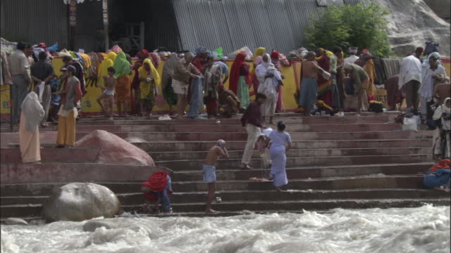 People bathe and wash clothes on steps by river, Gangotri, India Available in HD.