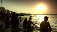 People bathe in the River Ganges as the sun sets.