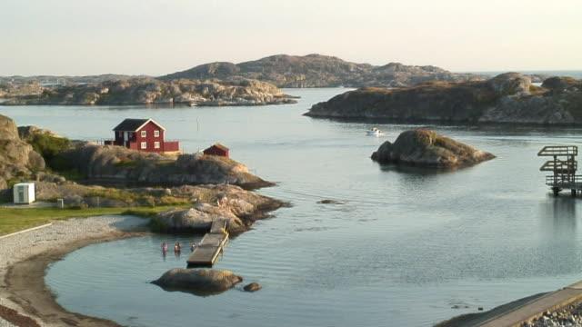 WS HA People bathing in sea, boat passing hilly islands in background / Sharhamn, Tjorn Island, Bohuslan, Sweden