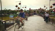 MS People bicycles and mopeds crossing ornamented bridge / Hoi An, Quang Nam, Vietnam