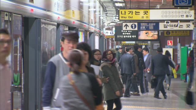 People boarding and disembarking subway trains at Seoul station