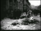 B/W 1956 people burning piles of Soviet books in street during Hungarian revolution / newsreel