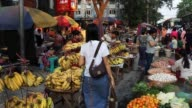 People buy and sell fruit and vegetables in a street market on February 15 2013 in Yangon Burma Myanmar is going through rapid political and economic...