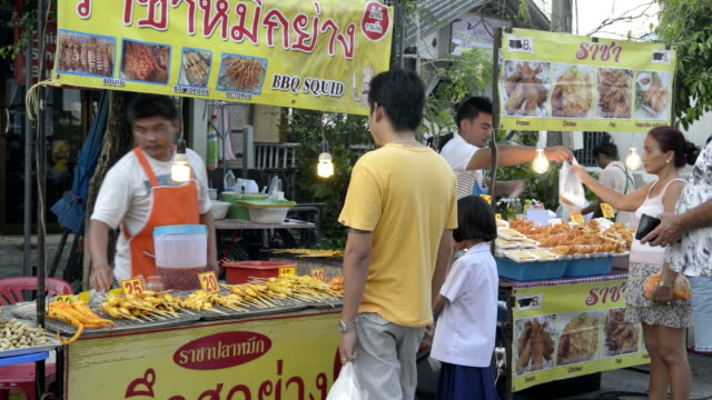 People buy grilled squid in a food stall