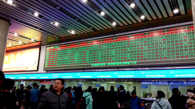 People buy tickets at Beijingxi Railway Station before the travel rush season as families gather to celebrate the forthcoming Chinese Spring Festival...