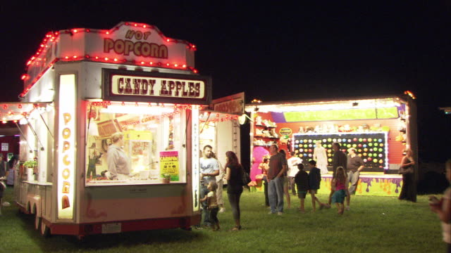 WS PAN People buying candy apples and popcorn, arcade game in background, night / Hartsdale, New York, USA