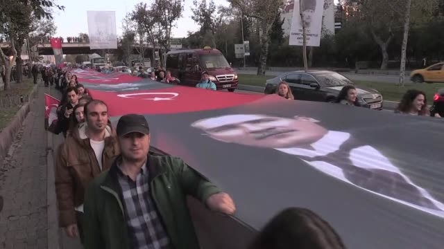 People carrying Turkish flags and banners depicting Mustafa Kemal Ataturk who is the founder of the Republic of Turkey march from Besiktas district...