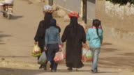 MS ZO People carrying vegetable and walking through street / Egypt