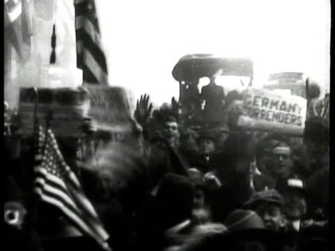 People celebrating in street MS Crowd in street people holding up newspapers MS President Woodrow Wilson standing outside w/ General John J...