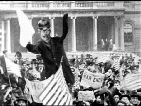 People celebrating waving hands hats WS Crowd waving flags newspapers cutout of Kaiser Wilhelm II PAN Crowd TIMES SQUARE Men on truck 'strangling'...