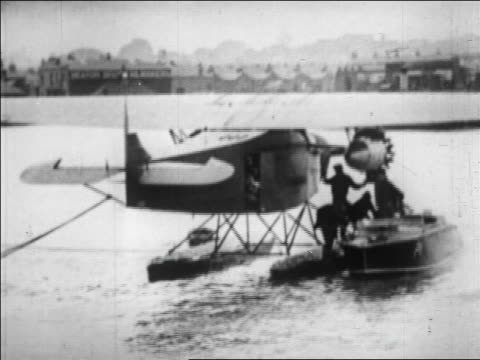 B/W 1928 people climbing from Amelia Earhart's seaplane to boat / shoreline in background / England / news
