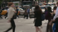 People cross the street on crosswalks on a busy day in Manhattan.  Traffic waits at a light for them to cross the street.
