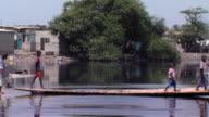 WS PAN People crossing canal on footbridge, Tamale, Ghana