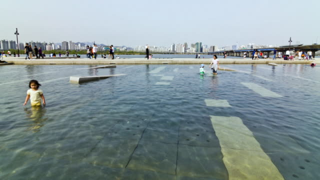 WS T/L People crossing small bridge in Yeouido Hangang Riverside Park / Seoul, South Korea
