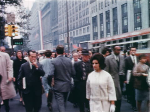 1960 people crossing street with bus passing in background / NYC / newsreel