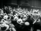 B/W 1931 people crowding on city sidewalk to see Al Capone exiting building