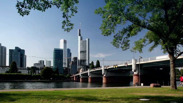 WS People cycling and jogging along River Main with Untermain Bridge, Commerzbank Tower and skyscrapers in background / Frankfurt, Hessen, Germany