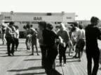 People dance the twist on a pier