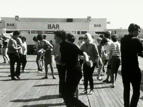 People dance the twist on a pier