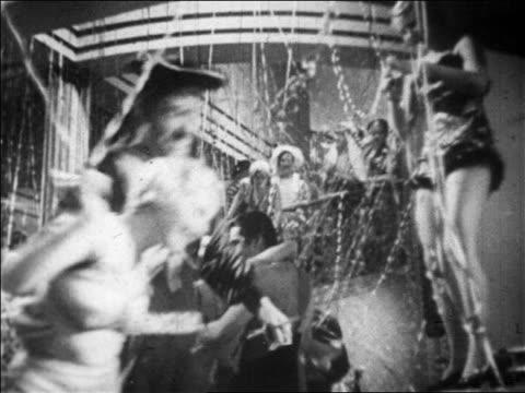 B/W 1928 people dancing amidst streamers in nightclub as people on balcony in background look on / newsreel