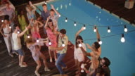 CS People dancing and having a good time at an evening party by the pool