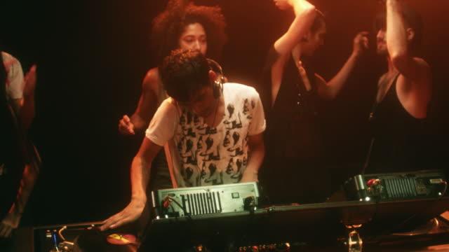 MS TU TD SLO MO People dancing around DJ in raised booth in night club / New York City, New York, USA