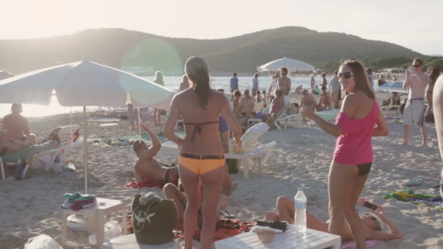 MS People dancing at sunset on Playa de las Salinas beach / Ibiza, Spain