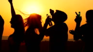 People dancing at sunset, slow motion.