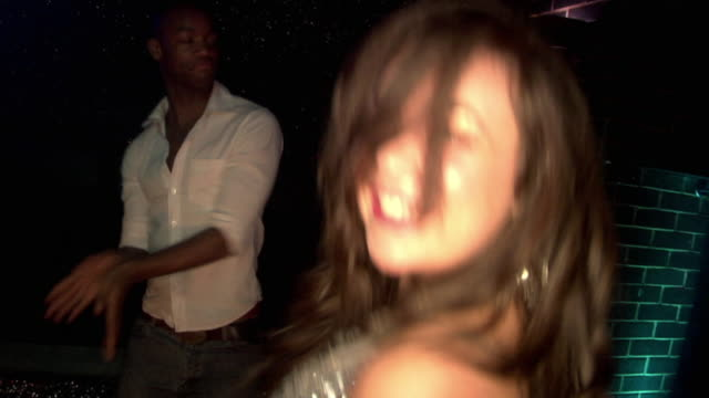 MS SLO MO PAN People dancing  in nightclub, London, England
