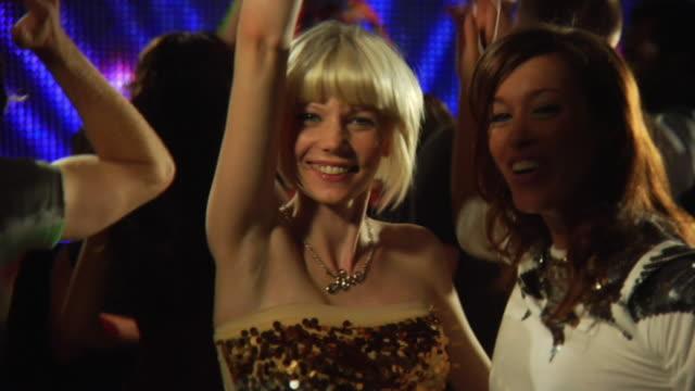 MS SLO MO People dancing in nightclub while DJ playing records / London, UK