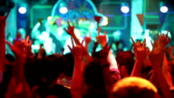 People dancing with arms raised in nightclub, Concert