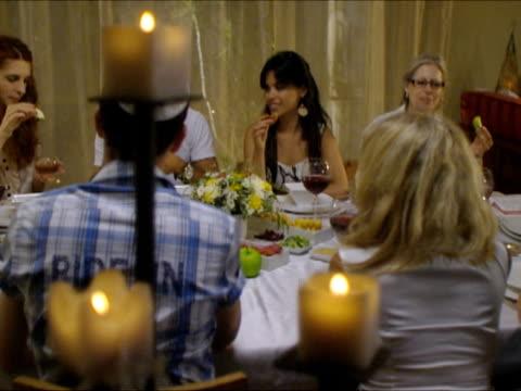 MS PAN People dipping apples in honey sitting around dinner table during Rosh Hashanah / Beit Yitzhak, Israel